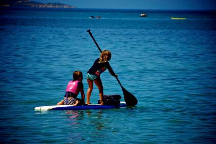 Our neighbor at the park, Bea, lent us her paddle board. The girls were up an moving around on it within seconds.