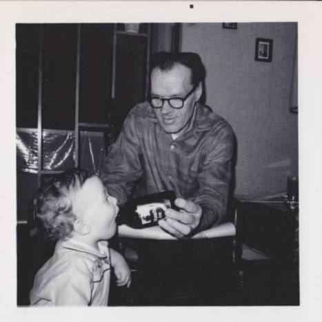 Grampa, here busted by a photographer, feeding me a sip of O'Keefe. The bottle gives some sense of scale - have a look at how big his hands were.